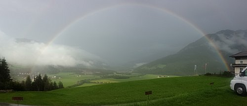 De zon komt en de regenboog wordt zichtbaar